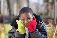 African american male child playing outdoors. African american boy outdoor autumn portrait wearing colorful mittens Stock Photos