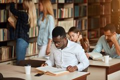 African american male college studen preparing for exams in the library. stock photos