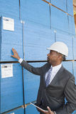 African American male contractor inspecting wooden planks while holding tablet PC Royalty Free Stock Photo