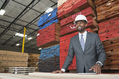 An African American male contractor standing in front of stacked wooden planks Stock Photo