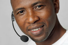 African American male customer service representative or call center worker. Operator, support staff speaking with head set Stock Image