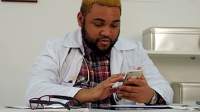 African american male doctor getting excited over phone message stock footage