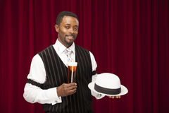 African American male dressed in a retro mobster suit holding a beer an his hat. An African American male bartender in a retro suit holds his hat and a beer royalty free stock photos