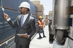 African American male engineer inspecting planks while female worker standing by flatbed truck