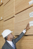 African American male engineer inspecting wooden planks Royalty Free Stock Photos