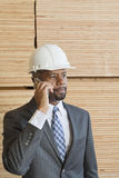 African American male engineer on phone call with stacked wooden planks in background Royalty Free Stock Photography