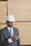 African American male engineer using cell phone with stacked wooden planks in background Stock Photo