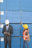 African American male engineer working on tablet PC while female industrial worker checking wooden planks Royalty Free Stock Image