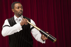 African American male explorer in retro suit. A well dressed African American male explorer in a retro suit holds a telescope while looking off into the distance stock photos
