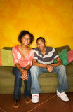African-American male and female on couch Royalty Free Stock Photos