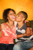 African-American male and female on couch. Good-looking single-parent mom and son sitting on sofa Stock Photos