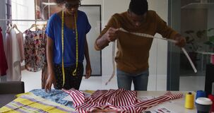African american male and female fashion designers taking measurements of clothing