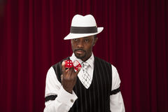African American male gambler in retro suit holding over size dice. A well dressed African American male wearing a retro suit and hat holding over size dice royalty free stock photography