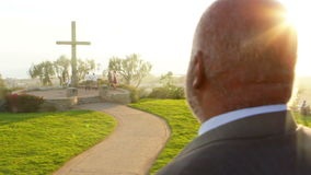 African American Male Looks over sunset with large wooden cross in distance. Sunbeams stream through the shot. Large hillside outside park. Dolly camera right stock video footage