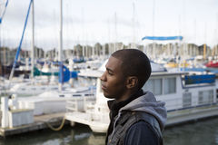 African American male model pondering at a boat marina Stock Image