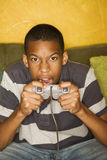 African-american male playing video games. Handsome young man Playing a Video Game with Handheld Controllers Royalty Free Stock Photo