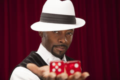 African American male in retro suit holding oversize dice. Royalty Free Stock Image