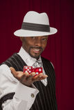 African American male in retro suit holding oversize dice. An African American male wearing a retro mobster suit holding over size dice royalty free stock photo