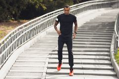 African-american male runner running down steps outdoors. African-american male runner running down the steps in the park stock photo