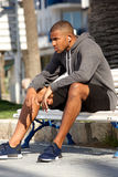 African american male runner sitting outdoors on bench. Portrait of african american male runner sitting outdoors on bench Royalty Free Stock Photo