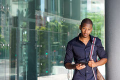 African american male student standing outside with tablet and bag. Portrait of african american male student standing outside with tablet and bag Royalty Free Stock Image