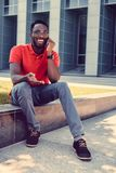 African American male talking by smartphone. Positive smiling African American male talking by smartphone on a street Royalty Free Stock Photos