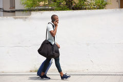 African american male traveler walking outside and talking on cell phone. Full length side portrait of african american male traveler walking outside and talking Stock Photo