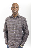 African American Man. Male African American standing with hands in pockets wearing a check shirt Royalty Free Stock Photo