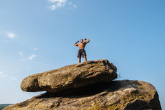 African american man athlete stands on a rock against the blue cloudy sky.  Stock Images