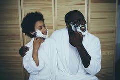 African American man in bathrobe teaches son stock photography
