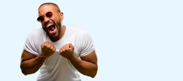 African young man  over white background. African american man with beard happy and excited celebrating victory expressing big success, power, energy and Stock Images
