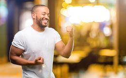 African young man  over white background. African american man with beard happy and excited celebrating victory expressing big success, power, energy and Royalty Free Stock Images