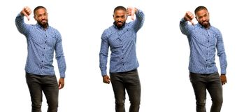 African young man isolated over white background. African american man with beard showing thumbs down unhappy sign of dislike, negative expression and Stock Photo