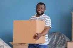 African-American man with box indoors. Moving into new house royalty free stock images