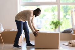 African-American man with box indoors. Moving into new house royalty free stock photo