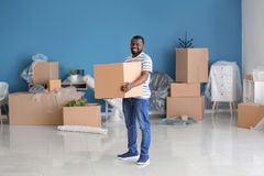 African-American man with box indoors. Moving into new house royalty free stock image