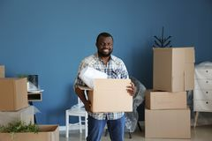 African-American man with box indoors. Moving into new house royalty free stock photos
