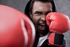 African American man with boxing gloves. Angry African American boxer making punch. Concept of rough sports and aggression stock image