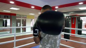 The guy with the girl are resting in natureman stands in the corner of the ring with boxing gloves around his neck holds a phone. African american man boxing in stock video