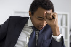 African American man brainstorming. Close up of an African American clerk sitting in his office with white furniture and thinking. His fist is near his forehead Stock Photos