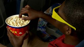 African American man with a bucket of popcorn is stock video footage