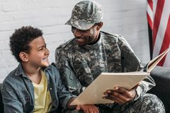 African american man in camouflage clothes and boy. Reading book royalty free stock photos