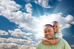 African American Man with Child Over Sky. Happy African American Man with Child Over Blue Sky, Clouds and Sun Rays Stock Photo
