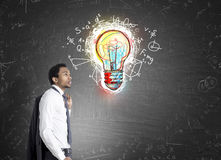 African American man and colorful light bulb Royalty Free Stock Photos