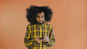 African American man with curly hair is thinking before send message on Orange background. Concept of emotions stock footage