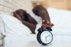 African American man does not want to wake up stock photo
