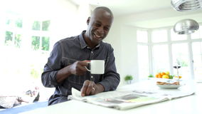 African American Man Eating Breakfast And Reading Newspaper. African American man sitting at kitchen counter reading newspaper whilst drinking cup of coffee.Shot stock video