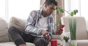 Man having breakfast while using mobile phone on sofa. African american man eating cookie and drinking coffee while using mobile phone on sofa stock video
