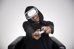 African American man enjoying a vr game. African American guy in a black hoodie is playing a virtual reality game. His tongue is stuck out. He is holding a royalty free stock photos