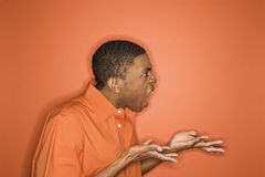 African-American man expressing anger. Side view of young African-American man on orange background expressing anger towards unseen person Royalty Free Stock Photo
